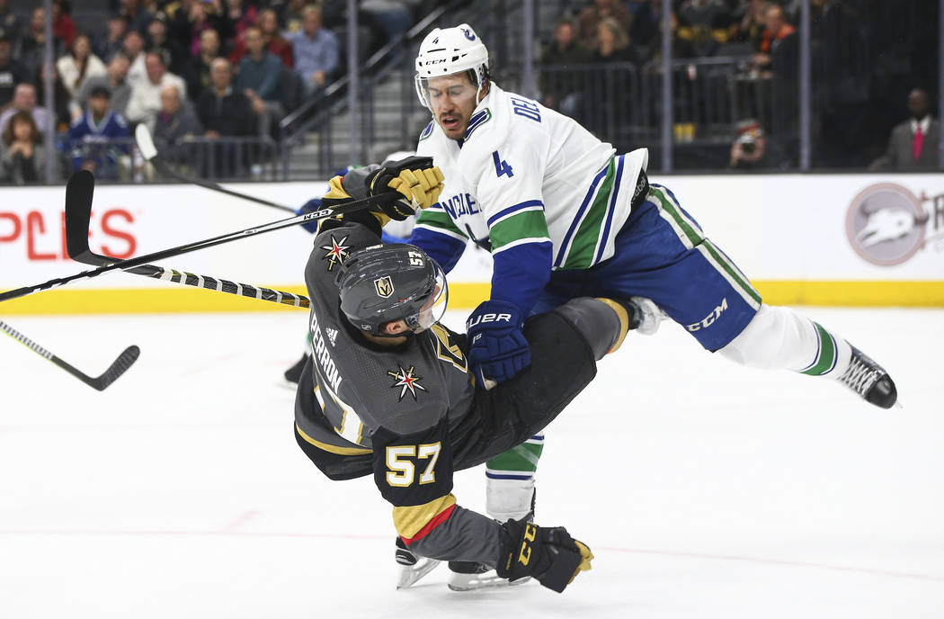 Vancouver Canucks defenseman Michael Del Zotto (4) knocks down Golden Knights left wing David Perron (57) during the first period of an NHL hockey game at T-Mobile Arena in Las Vegas on Tuesday, M ...