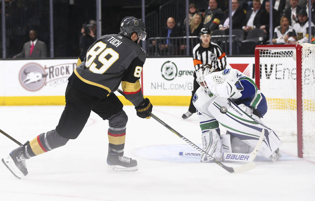 Golden Knights right wing Alex Tuch (89) attempts to score as Vancouver Canucks goaltender Jacob Markstrom (25) defends during the first period of an NHL hockey game at T-Mobile Arena in Las Vegas ...