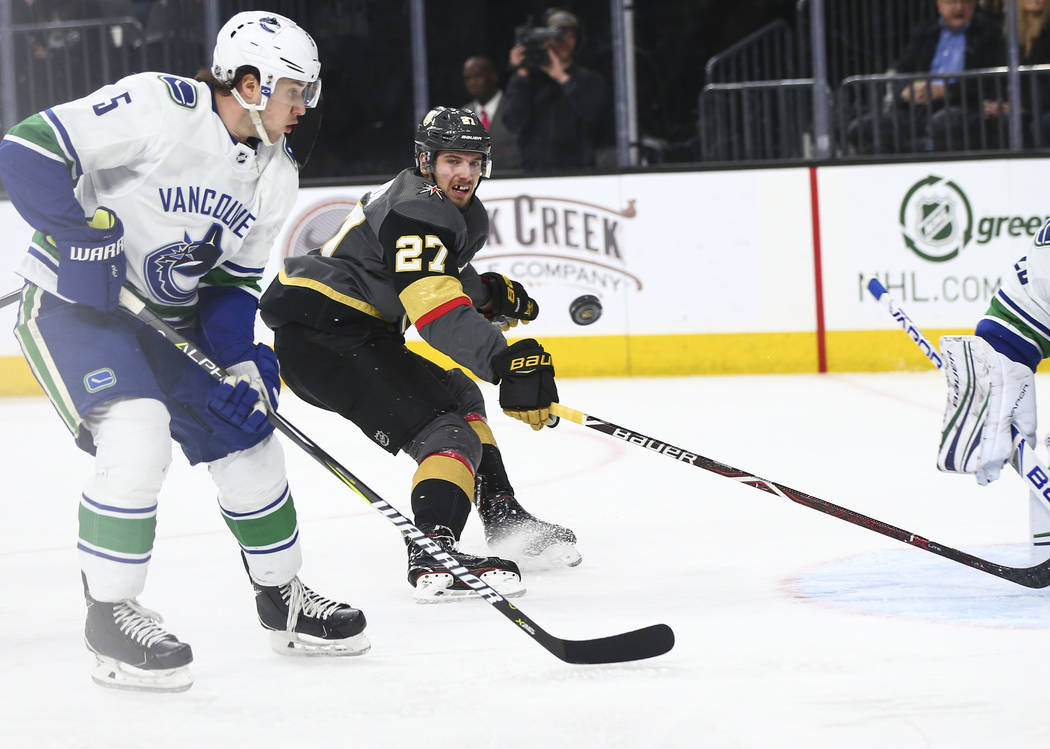 Golden Knights defenseman Shea Theodore (27) eyes the puck as it flies past Vancouver Canucks defenseman Derrick Pouliot (5) during the first period of an NHL hockey game at T-Mobile Arena in Las  ...