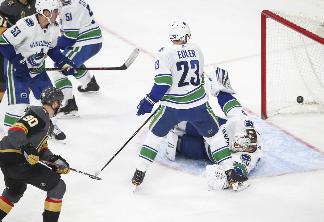 Golden Knights left wing Tomas Tatar (90) scores against Vancouver Canucks goaltender Jacob Markstrom (25) during the second period of an NHL hockey game against the Vancouver Canucks at T-Mobile  ...