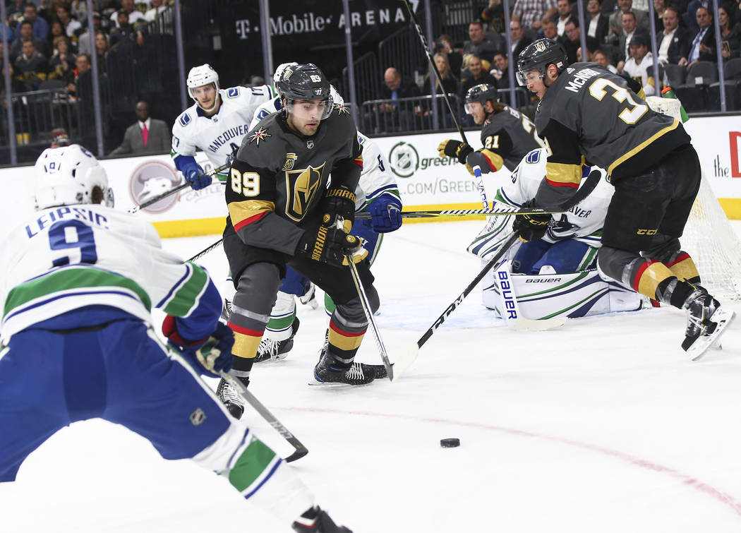 Golden Knights right wing Alex Tuch (89) watches the puck as Vancouver Canucks left wing Brendan Leipsic (9) defends during the first period of an NHL hockey game at T-Mobile Arena in Las Vegas on ...