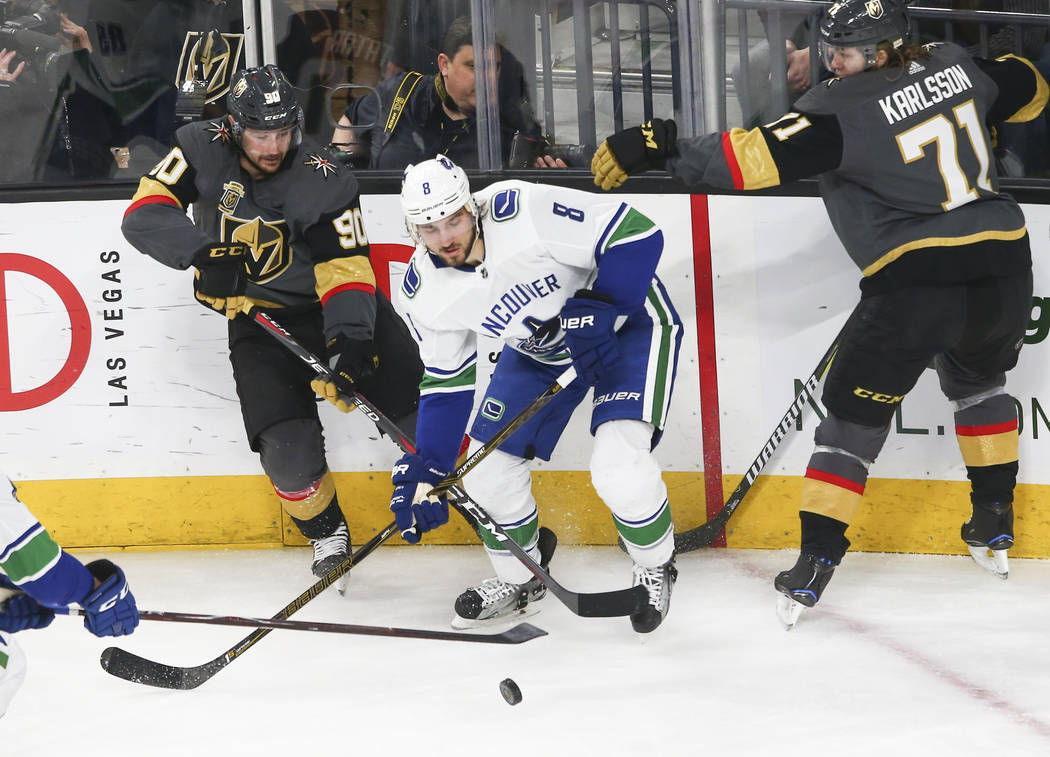 Golden Knights left wing Tomas Tatar (90) and center William Karlsson (71) go after the puck against Vancouver Canucks defenseman Christopher Tanev (8) during the second period of an NHL hockey ga ...