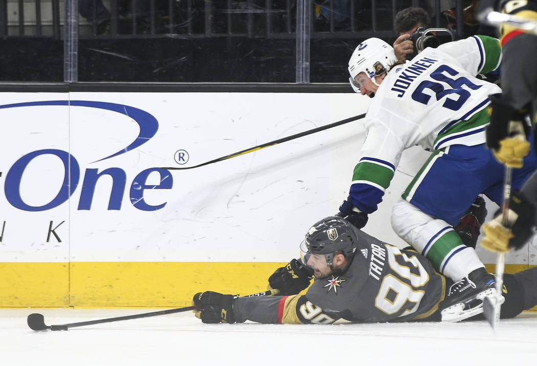 Golden Knights left wing Tomas Tatar (90) tries to keep control of the puck as he falls to the ice as Vancouver Canucks left wing Jussi Jokinen (36) defends during the third period of an NHL hocke ...