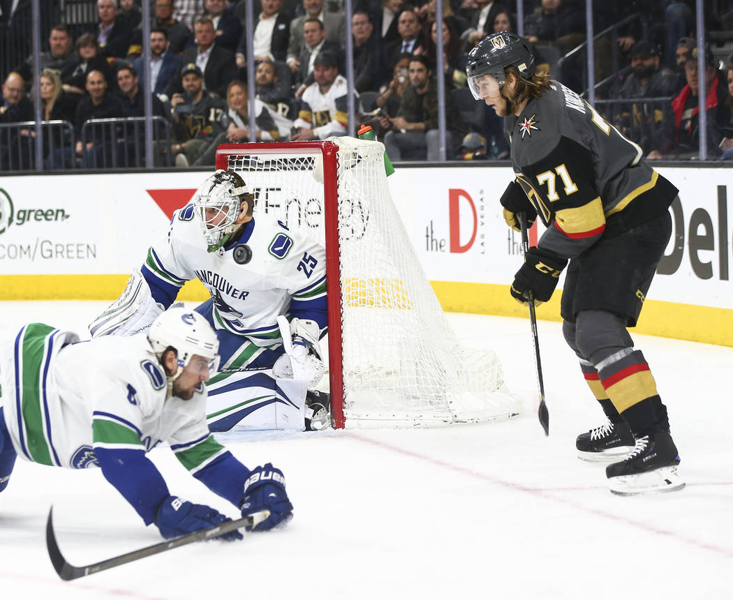 The puck flies between Vancouver Canucks defenseman Christopher Tanev (8) and goaltender Jacob Markstrom (25) as Golden Knights center William Karlsson (71) looks on during the third period of an  ...