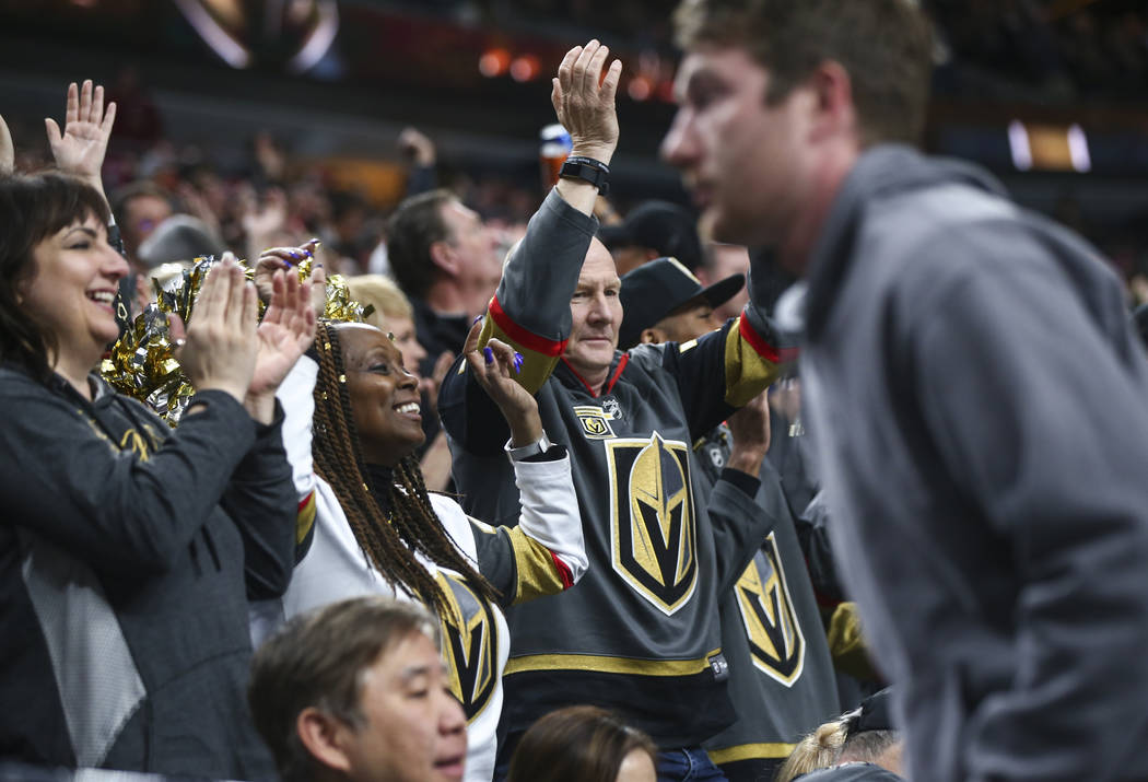 Golden Knights fans celebrate a goal by Golden Knights left wing Pierre-Edouard Bellemare, not pictured, against the Vancouver Canucks during the first period of an NHL hockey game at T-Mobile Are ...