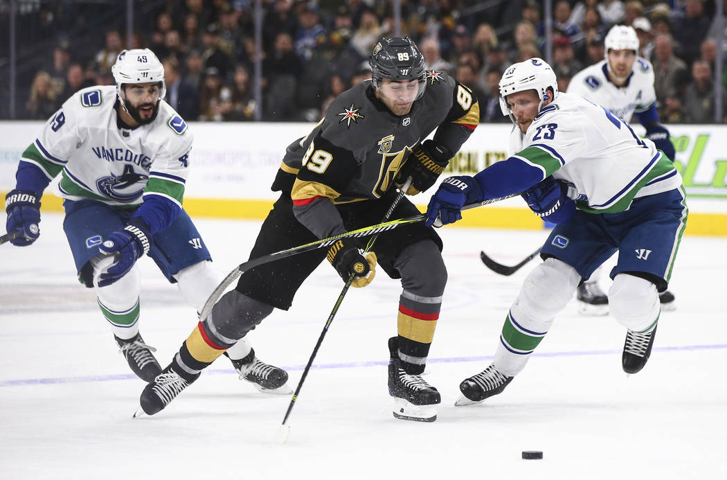 Golden Knights right wing Alex Tuch (89) moves the puck against Vancouver Canucks defenseman Alexander Edler (23) during the first period of an NHL hockey game at T-Mobile Arena in Las Vegas on Tu ...