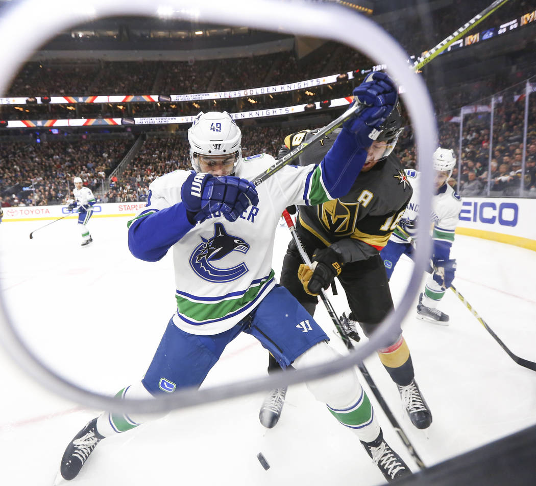 Golden Knights left wing James Neal (18) fights for control of the puck against Vancouver Canucks right wing Darren Archibald (49) during the first period of an NHL hockey game at T-Mobile Arena i ...