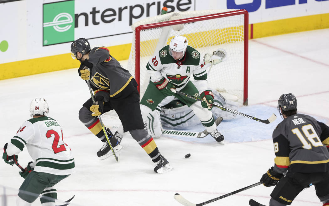 Vegas Golden Knights left wing Tomas Nosek, second left, takes a shot through his legs as Minnesota Wild defenseman Ryan Suter (20) defends the net during the first period of an NHL hockey game be ...