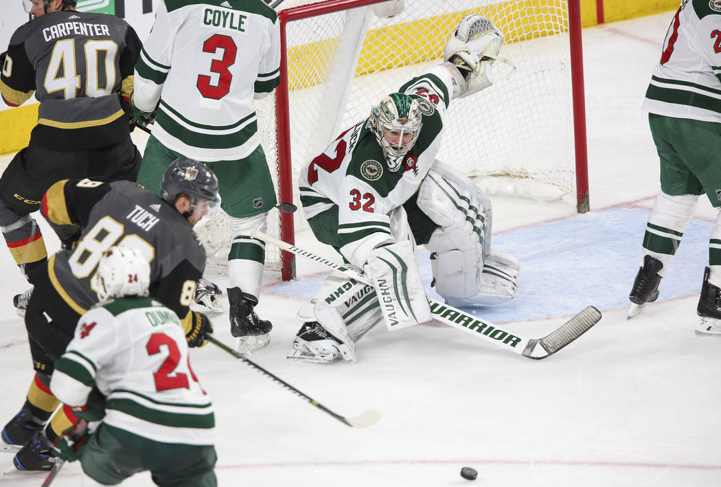 Minnesota Wild goaltender Alex Stalock (32) keeps his eye on the puck as Vegas Golden Knights right wing Alex Tuch (89) looks for a shot during the third period of an NHL hockey game between the V ...