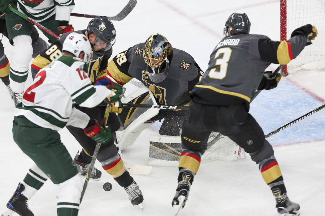 Vegas Golden Knights goaltender Marc-Andre Fleury (29), center, block the puck as Minnesota Wild center Eric Staal (12), Knights defenseman Nate Schmidt (88) and  Knights defenseman Brayden McNabb ...