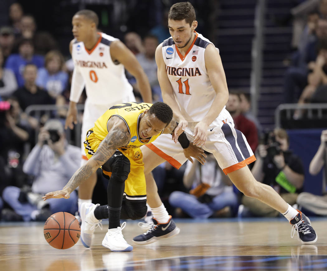 UMBC's Jairus Lyles (10) loses the ball as Virginia's Ty Jerome (11) defends during the first half of a first-round game in the NCAA men's college basketball tournament in Charlotte, N.C., Friday, ...