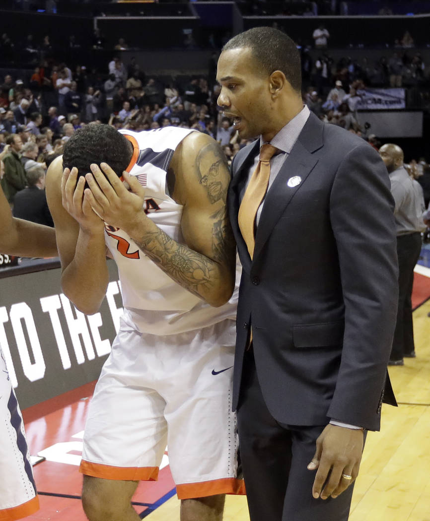 Virginia's Isaiah Wilkins, left, walks off the court after the team's 74-54 loss to UMBC in a first-round game in the NCAA men's college basketball tournament in Charlotte, N.C., Friday, March 16, ...