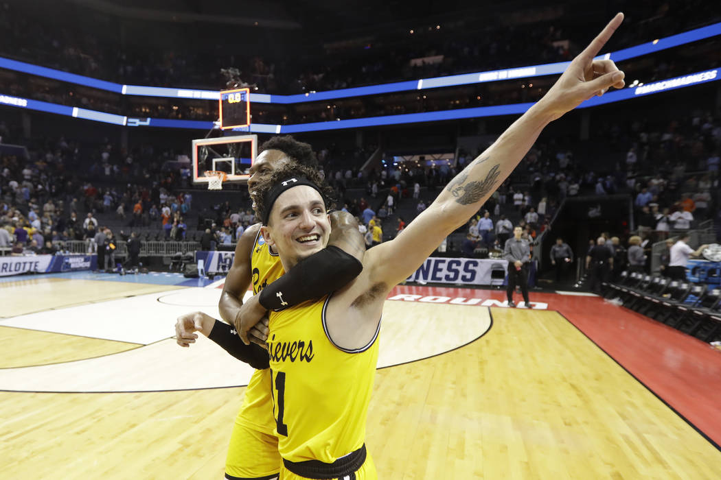 UMBC's K.J. Maura (11) and Jourdan Grant celebrate the team's 74-54 win over Virginia in a first-round game in the NCAA men's college basketball tournament in Charlotte, N.C., Friday, March 16, 20 ...