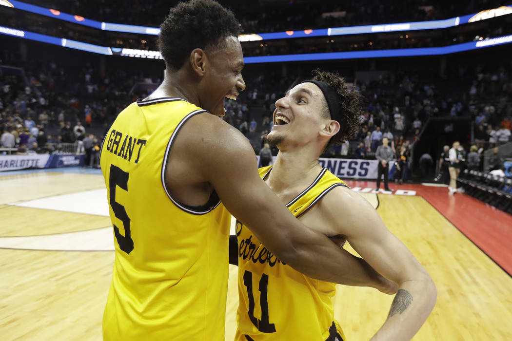UMBC's K.J. Maura (11) and Jourdan Grant (5) celebrate the team's 74-54 win over Virginia in a first-round game in the NCAA men's college basketball tournament in Charlotte, N.C., Friday, March 16 ...