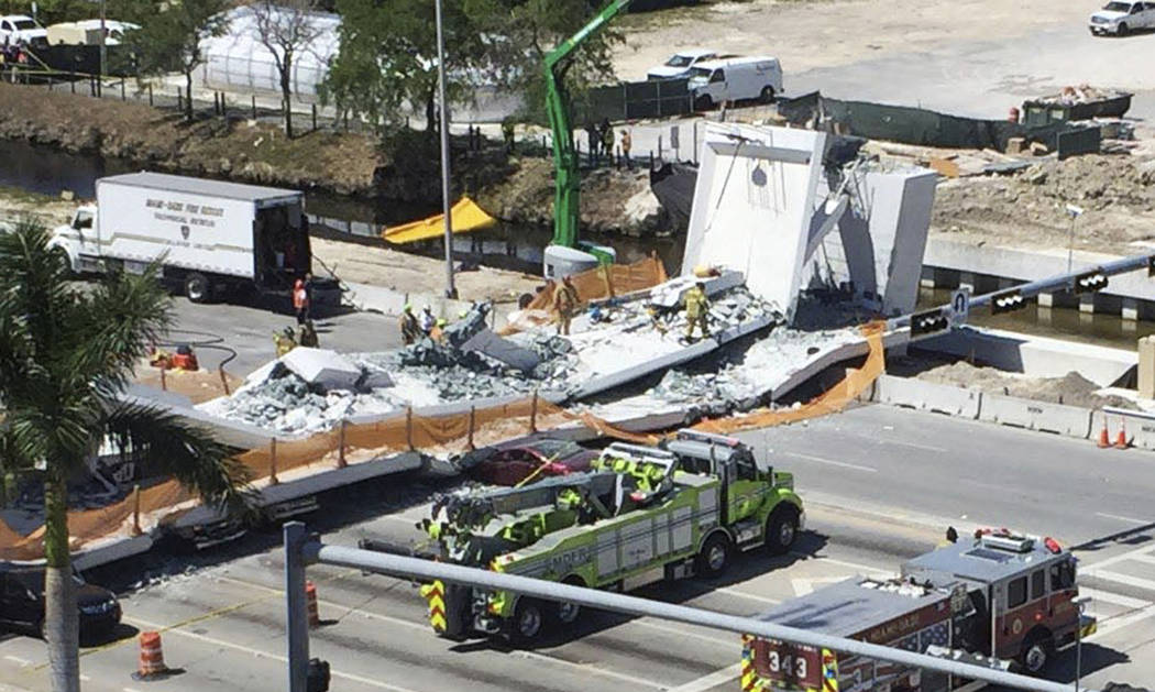 Emergency personnel respond to a collapsed pedestrian bridge at Florida International University on Thursday, March 15, 2018, in the Miami area. The brand-new pedestrian bridge collapsed onto a hi ...