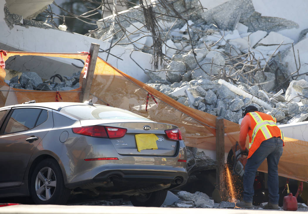 A worker uses a saw next to a crushed car under a section of a collapsed pedestrian bridge, Friday, March 16, 2018 near Florida International University in the Miami area.   The new pedestrian bri ...