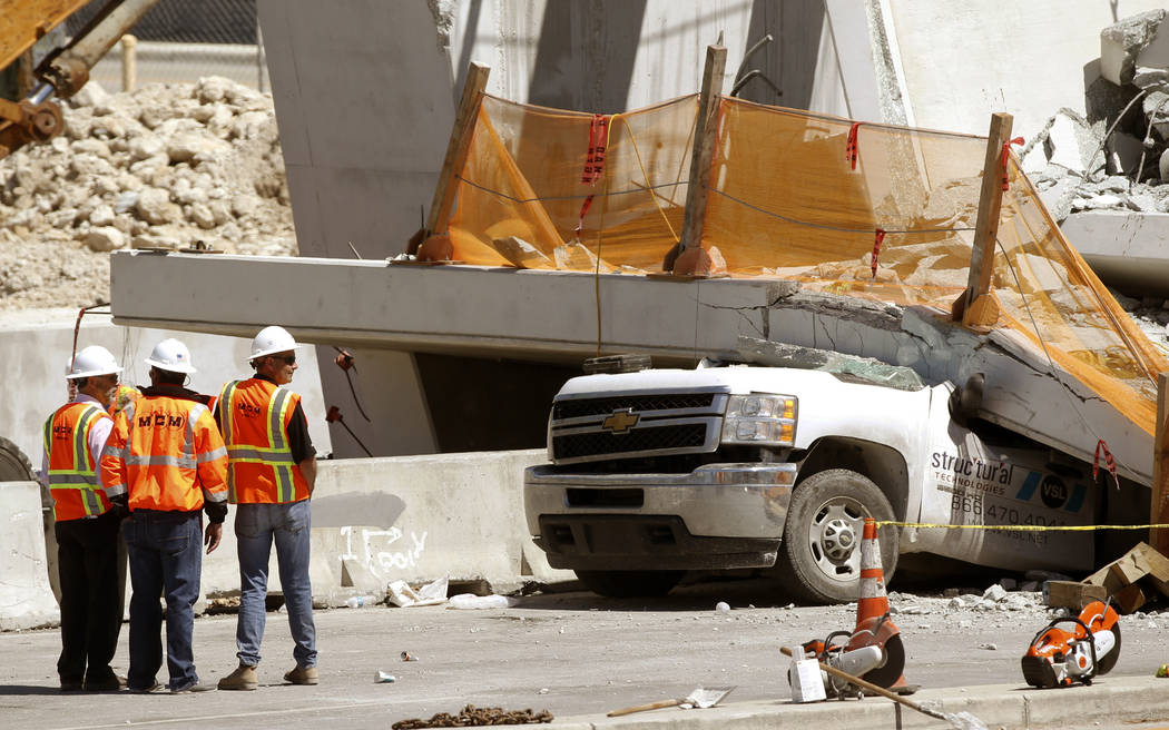 Workers stand next to a section of a collapsed pedestrian bridge, Friday, March 16, 2018 near Florida International University in the Miami area. The new pedestrian bridge that was under construct ...