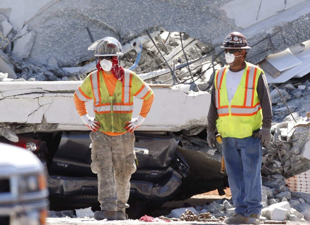 Workers stand in front of crushed cars under a section of a collapsed pedestrian bridge, Friday, March 16, 2018 near Florida International University in the Miami area. The new pedestrian bridge t ...