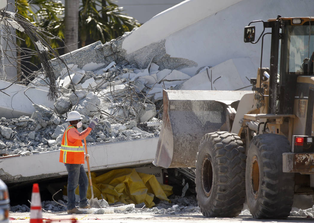 Workers use a front loader to clear debris from a section of a collapsed pedestrian bridge, Friday, March 16, 2018 near Florida International University in the Miami area. The new pedestrian bridg ...