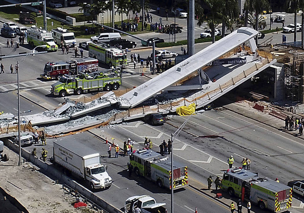 Emergency personnel respond after a brand-new pedestrian bridge collapsed onto a highway at Florida International University in Miami on Thursday, March 15, 2018. The pedestrian bridge collapsed o ...