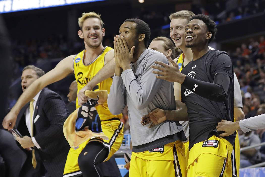 UMBC players celebrate a teammate's basket against Virginia during the second half of a first-round game in the NCAA men's college basketball tournament in Charlotte, N.C., Friday, March 16, 2018. ...