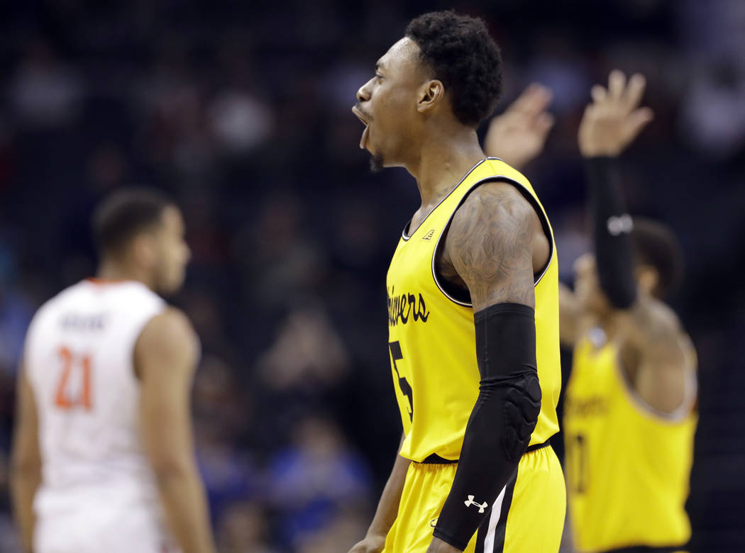 UMBC's Jourdan Grant (5) celebrates after a basket against Virginia during the second half of a first-round game in the NCAA men's college basketball tournament in Charlotte, N.C., Friday, March 1 ...