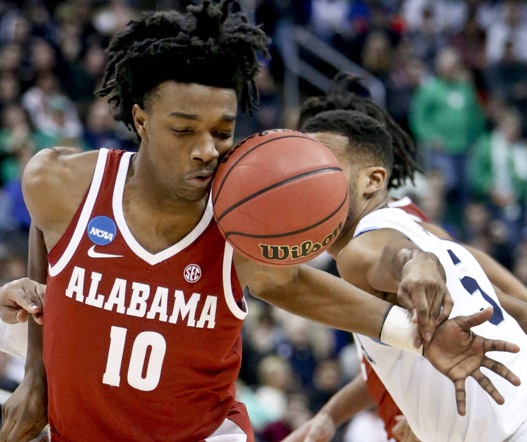 Alabama's Herbert Jones (10) drives towards the hoop as the ball hits him in the face while Villanova's Phil Booth defends during the first half of a second-round game in the NCAA men's college ba ...