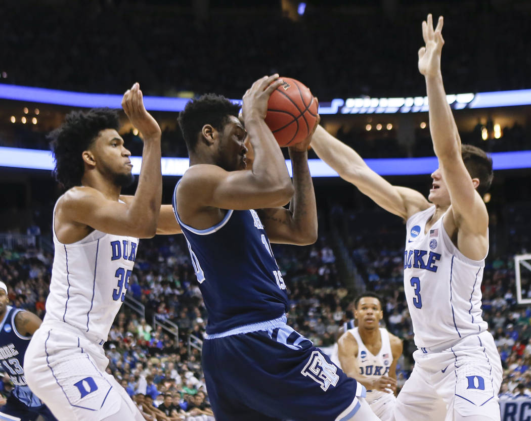Rhode Island's Cyril Langevine center, is double teamed by Duke's Grayson Allen (3) and Marvin Bagley III (35) as he looks to pass during the second half of a second-round game in the NCAA men's c ...