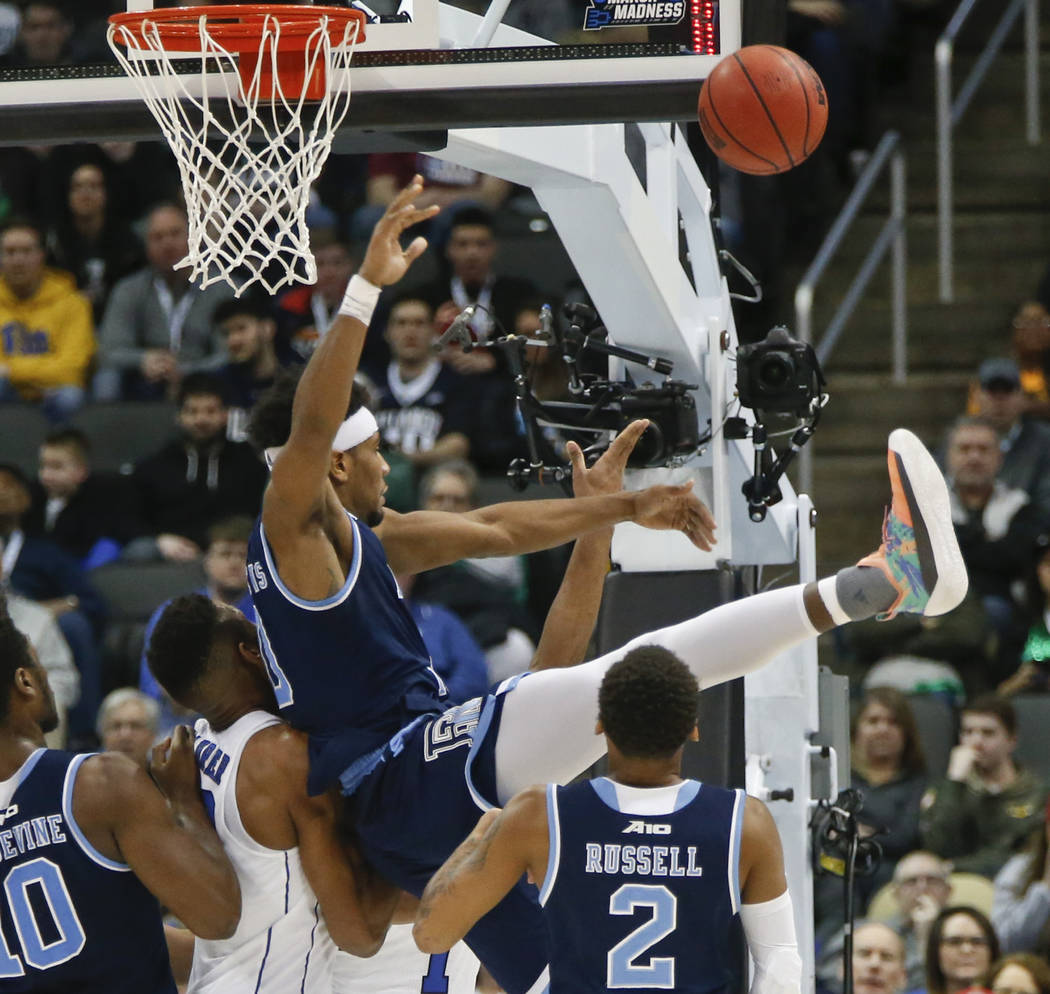 Rhode Island's E.C. Matthews, top, tumbles over Duke's Javin DeLaurier, center, as he tries to block a shot by Trevon Duval during the second half of a second-round game in the NCAA men's college  ...