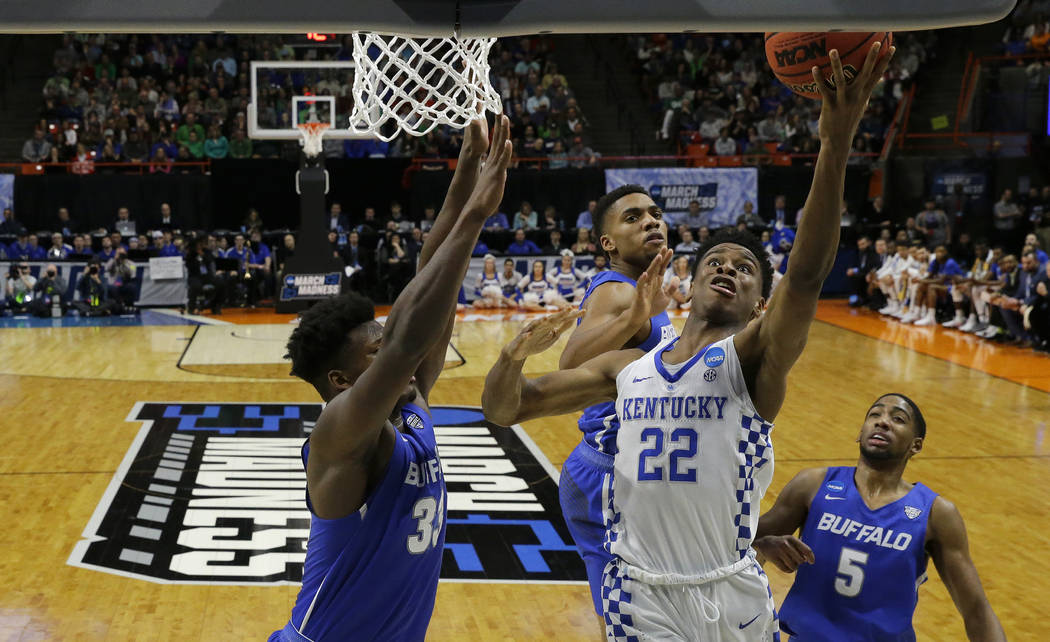 Kentucky guard Shai Gilgeous-Alexander (22) shoots as Buffalo forward Nick Perkins, left, defends during the second half of a second-round game in the NCAA men's college basketball tournament Satu ...