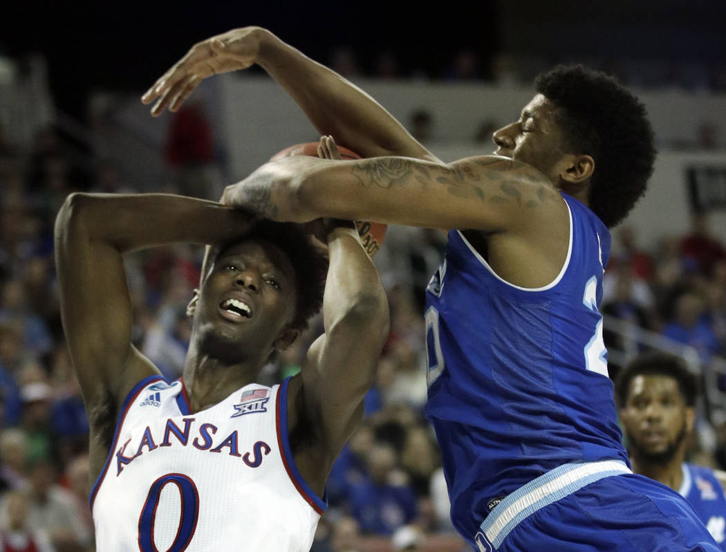 Kansas guard Marcus Garrett (0) is covered by Seton Hall forward Desi Rodriguez (20) during the first half of an NCAA men's college basketball tournament second-round game, Saturday, March 17, 201 ...