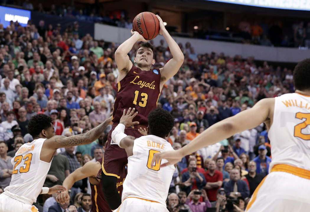 Loyola-Chicago guard Clayton Custer (13) shoots over Tennessee's Jordan Bowden (23) and Jordan Bone (0) and scores in the final seconds of a second-round game at the NCAA men's college basketball  ...