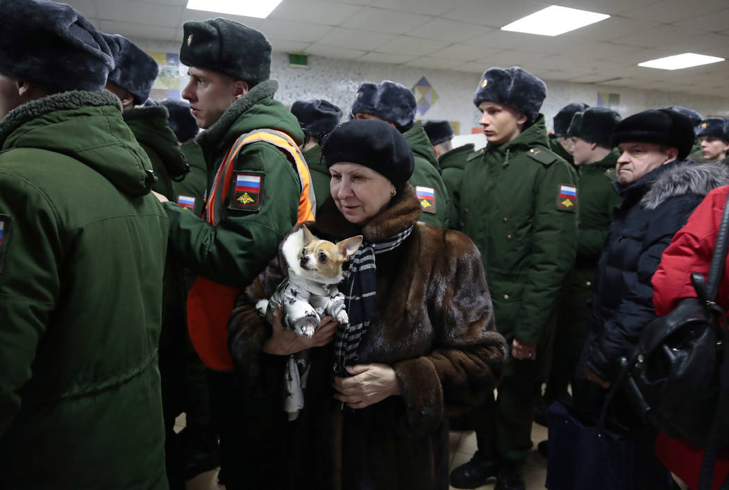 A woman with her dog lines up with Russian military personnel to vote in the presidential election in Moscow, Russia, Sunday, March 18, 2018. Russians are voting in a presidential election in whic ...