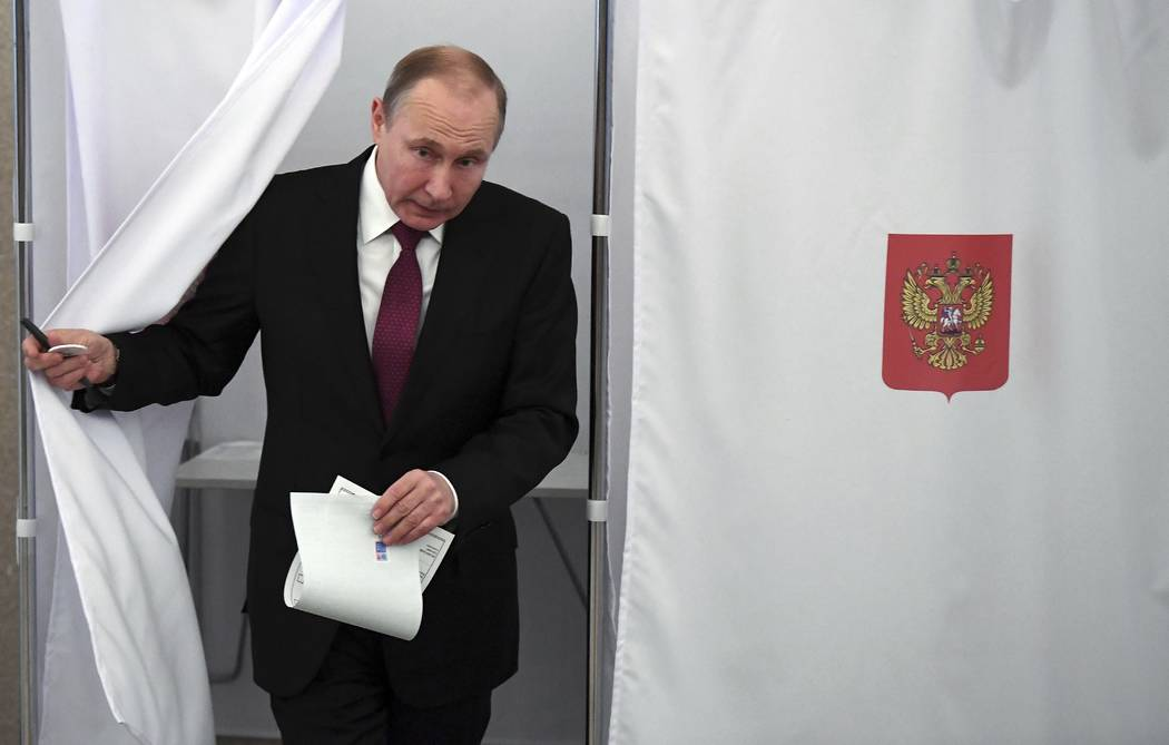 Russian President and Presidential candidate Vladimir Putin exits a polling booth as he prepares to cast his ballot during Russia's presidential election in Moscow, Russia, Sunday, March 18, 2018. ...