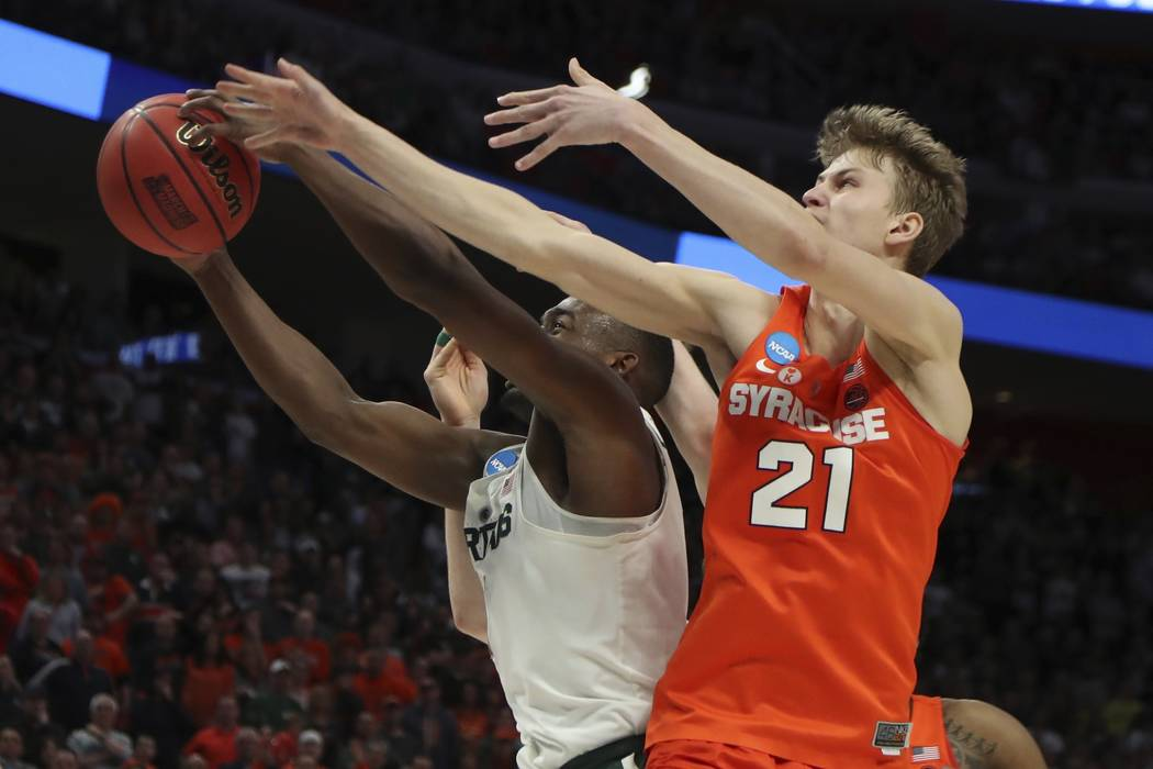 Michigan State guard Joshua Langford and Syracuse forward Marek Dolezaj (21) reach for the rebound during the second half of a second round game in the NCAA college basketball tournament, Sunday,  ...