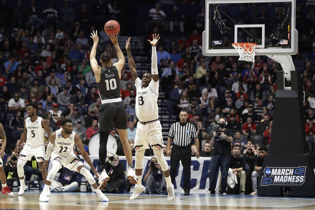 Nevada forward Caleb Martin (10) aims for the basket as Cincinnati forward Tre Scott (13) defends, during the first half of a second-round game in the NCAA college basketball tournament in Nashvil ...