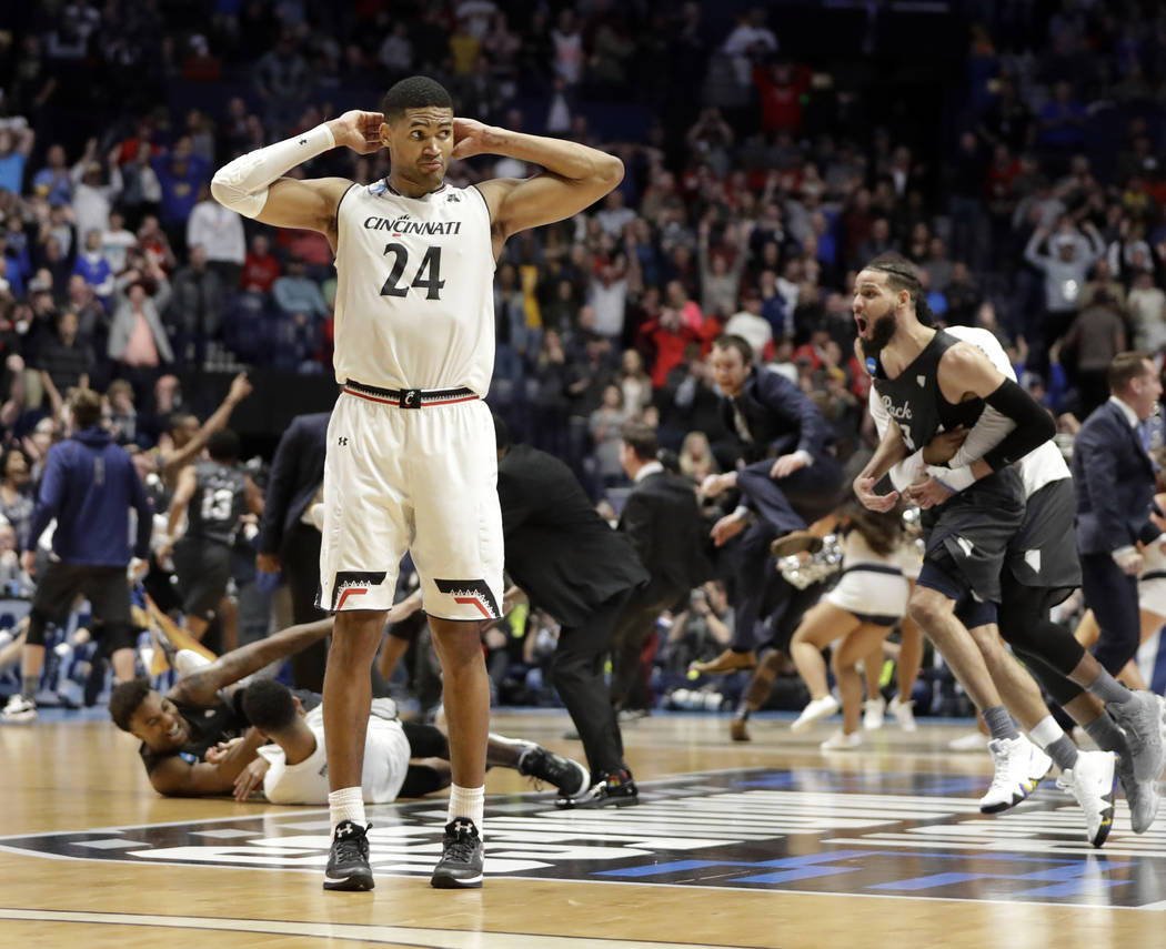 Cincinnati forward Kyle Washington (24) stands on the court as the Nevada team celebrates during the end of the second half of a second-round game in the NCAA college basketball tournament in Nash ...