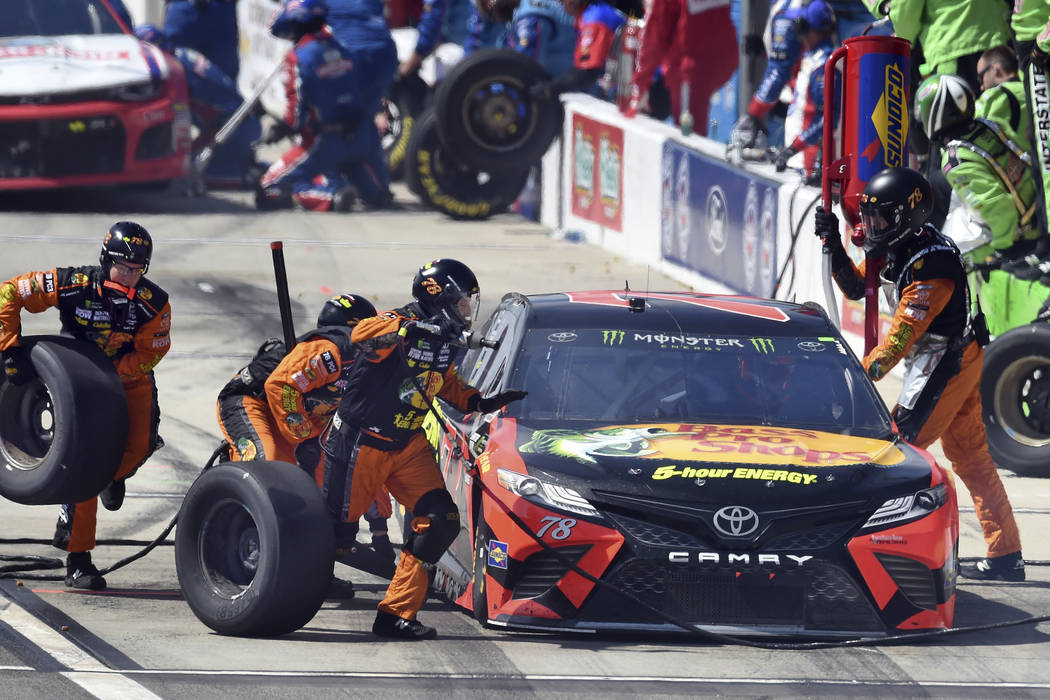 Martin Truex Jr. makes his first pit stop during the NASCAR Cup auto race Sunday, March 18, 2018, in Fontana, Calif. (AP Photo/Will Lester)