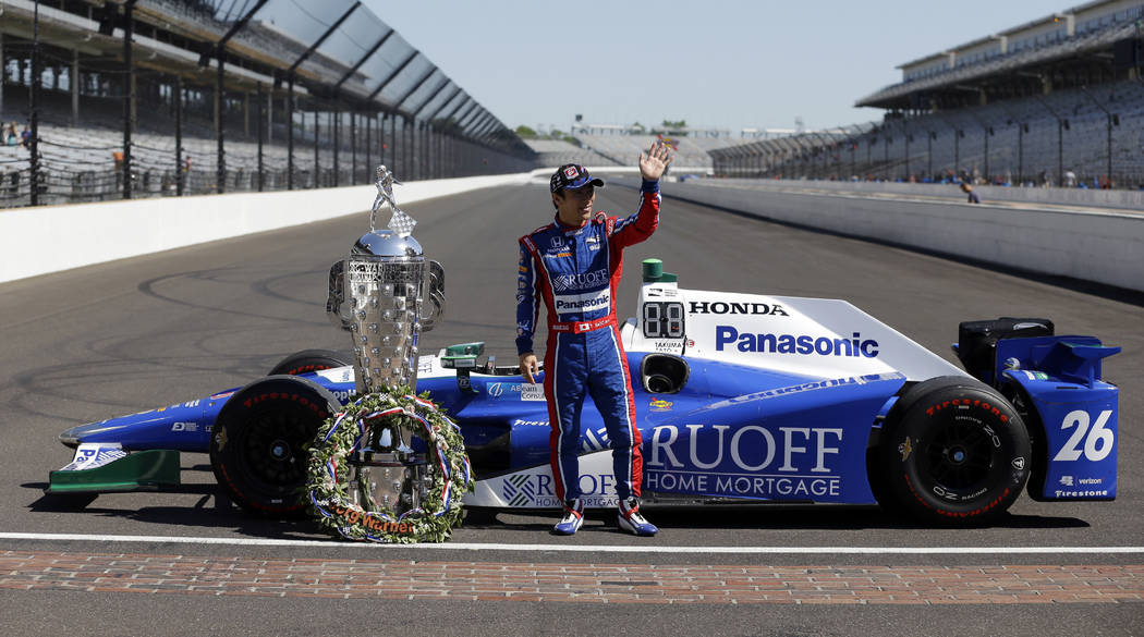 Indianapolis 500 champion Takuma Sato, of Japan, poses with the Borg-Warner Trophy during the traditional winners photo session on the start/finish line at the Indianapolis Motor Speedway in India ...
