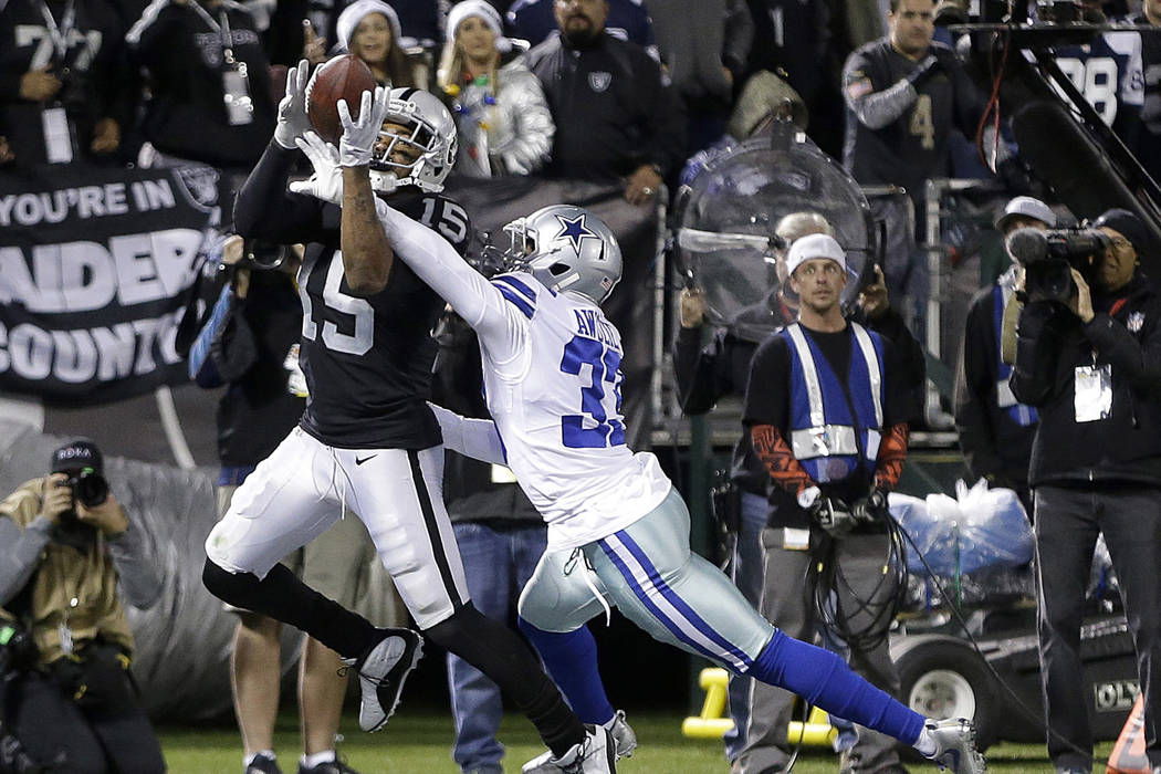 In this Dec. 17, 2017, file photo, Oakland Raiders wide receiver Michael Crabtree (15) catches a touchdown pass in front of Dallas Cowboys cornerback Chidobe Awuzie (33) during the second half of  ...