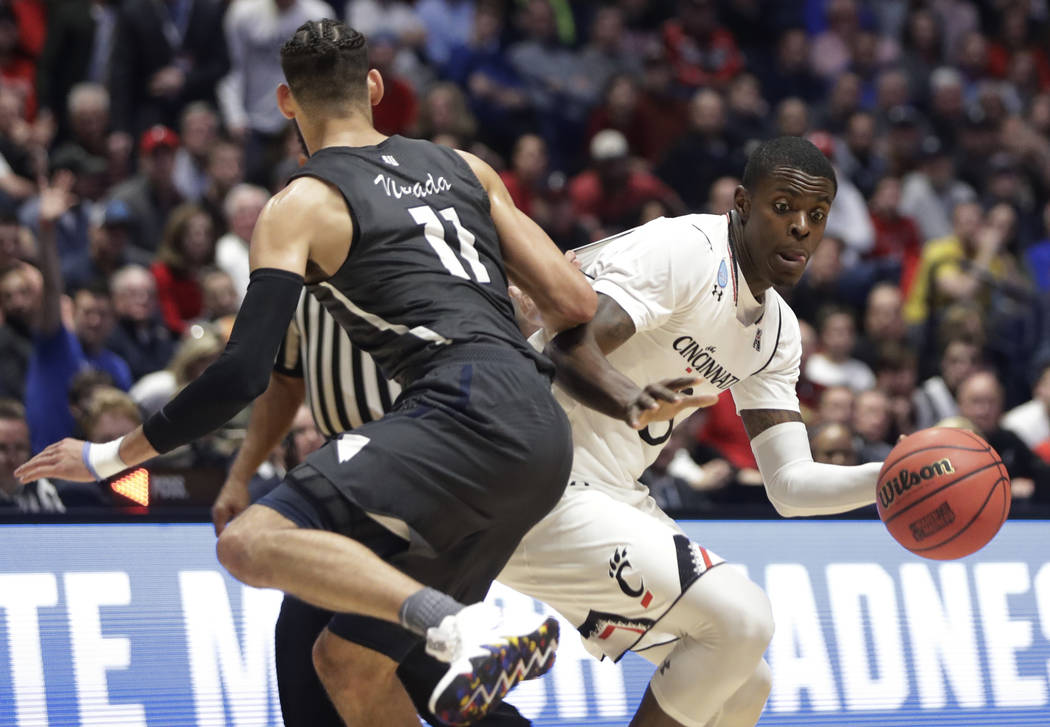 Cincinnati forward Tre Scott (13), right, dribbles the ball around Nevada forward Cody Martin (11), during the first half of a second-round game in the NCAA college basketball tournament in Nashvi ...