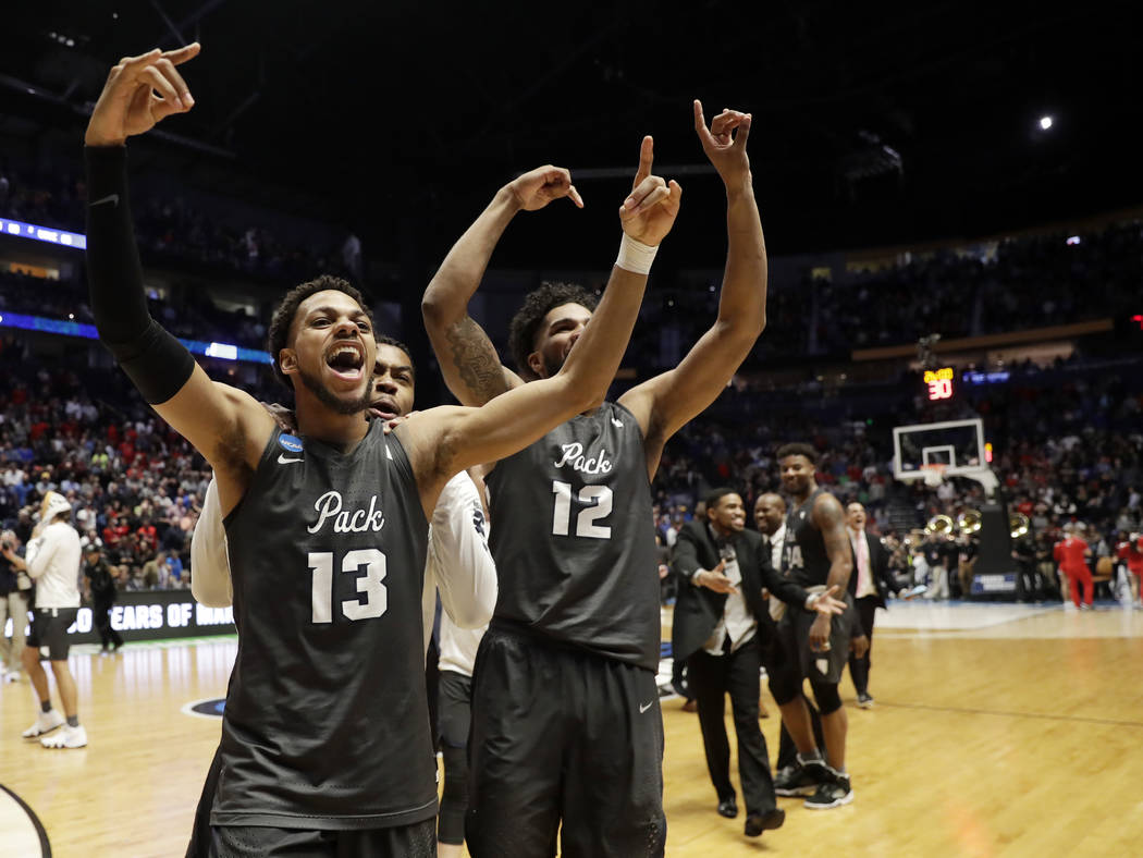 Nevada guard Hallice Cooke (13) and forward Elijah Foster (12) celebrate at the end end of the second half of a second-round game against Cincinnati, in the NCAA college basketball tournament in N ...