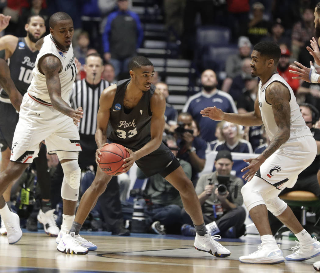 Nevada guard Josh Hall (33) sets up his game winning shot as Cincinnati forward Gary Clark (11) and Cincinnati guard Jacob Evans (1), defend, during the second half of a second-round game in the N ...