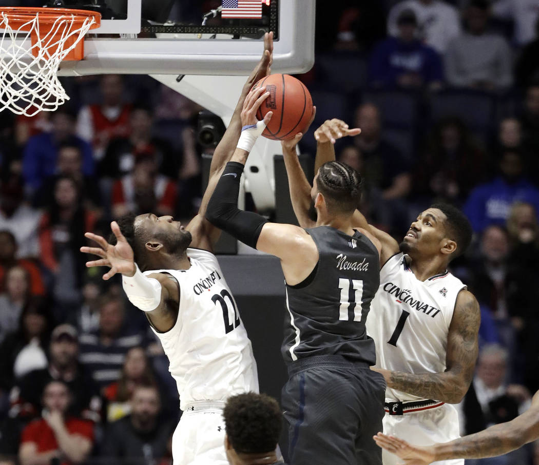 Nevada forward Cody Martin (11) drives to the basket as Cincinnati guard Jacob Evans (1) and forward Eliel Nsoseme (22) defend, during the first half of a second-round game in the NCAA college bas ...