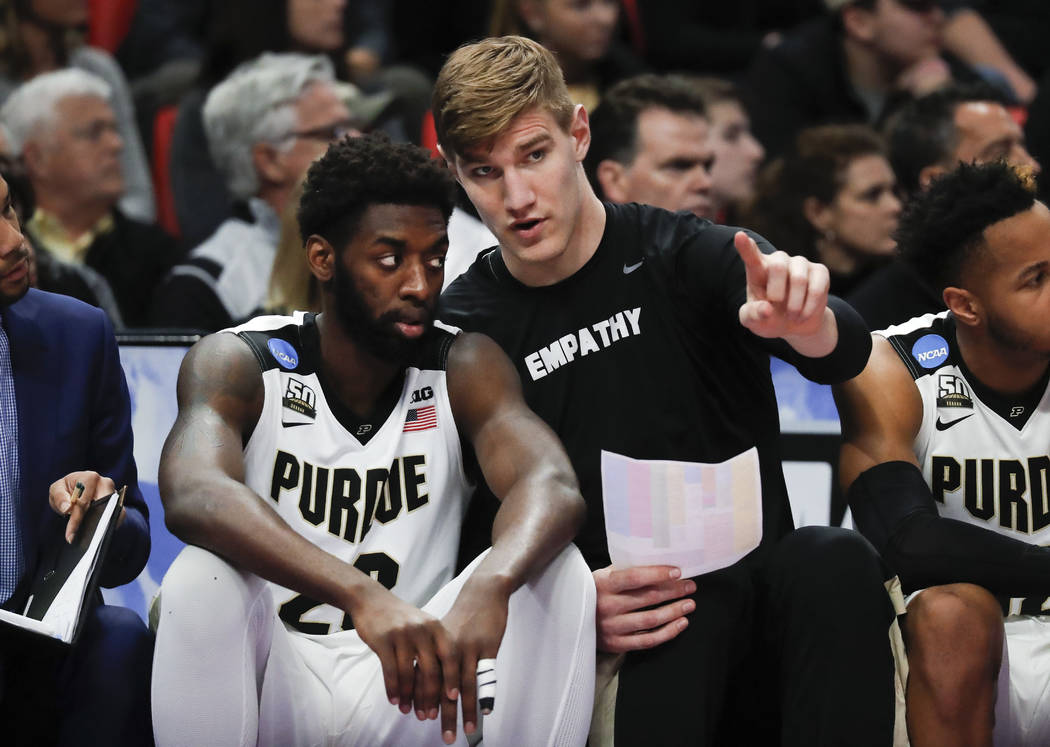 Purdue forward Jacquil Taylor, left, listens to Isaac Haas on the bench against Butler during the first half of an NCAA men's college basketball tournament second-round game in Detroit, Sunday, Ma ...