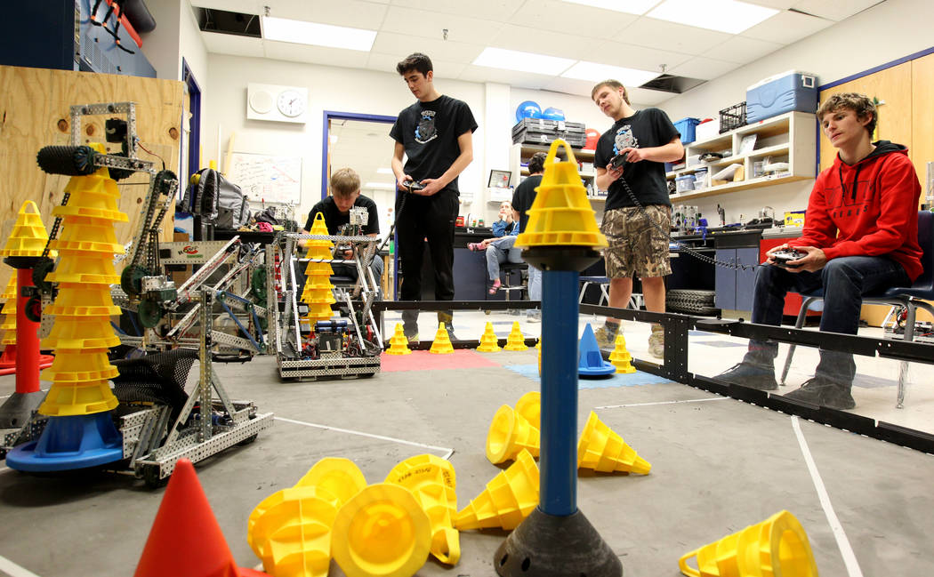 Lenny Montalbano, right, and his partner C.D. Perkins operate their robot to stack cones, competing against Tenton Moon, left, and Matteo Cipriani during Robot Club at Basic Academy of Internation ...