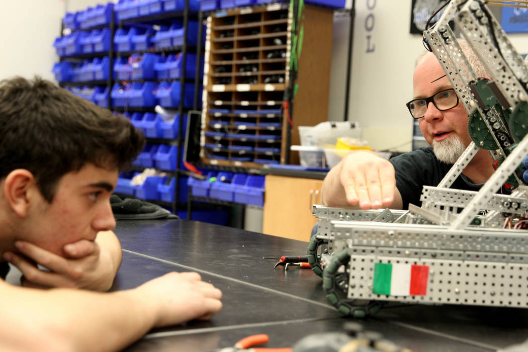 Basic Academy of International Studies in Henderson robotics advisor Mark Reed, right, gives a suggestion to senior Matteo Cipriani during Robot Club at the school Wednesday, March 21, 2018. The c ...