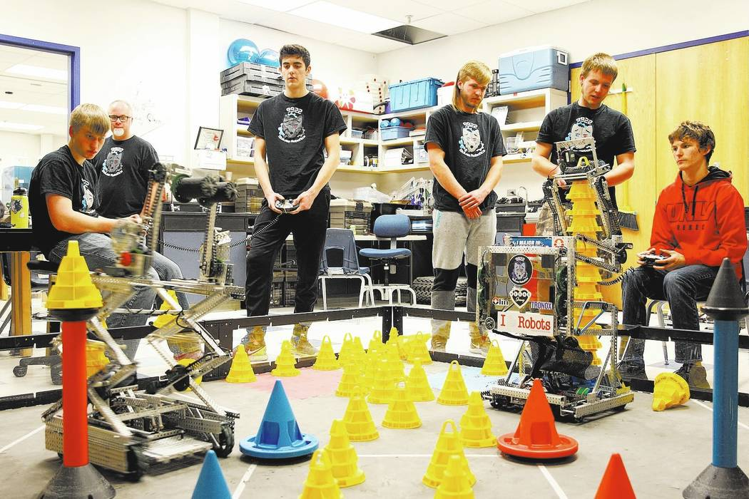 Tenton Moon, left, and Matteo Cipriani operate their robot to stack cones, competing against Lenny Montalbano, right, and his partner C.D. Perkins, second from right, during Robot Club at Basic Ac ...
