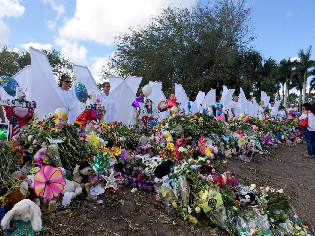 Seventeen people dressed as angels stand Sunday, Feb. 25, 2018, at the memorial outside Marjory Stoneman Douglas High School in Parkland, Fla., for those killed in a shooting on Feb. 14. Organizer ...