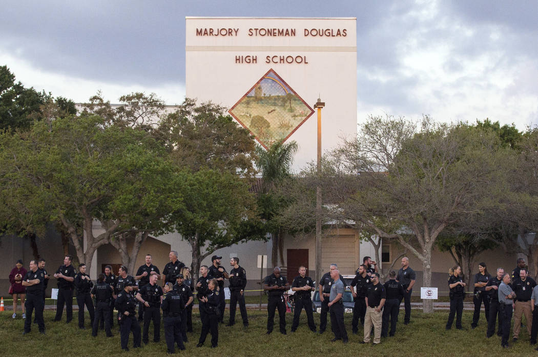 Law enforcement agents line up as students head back to school at Marjory Stoneman Douglas High School  on Wednesday, Feb. 28, 2018 in Parkland, Fla.  With a heavy police presence, classes resumed ...